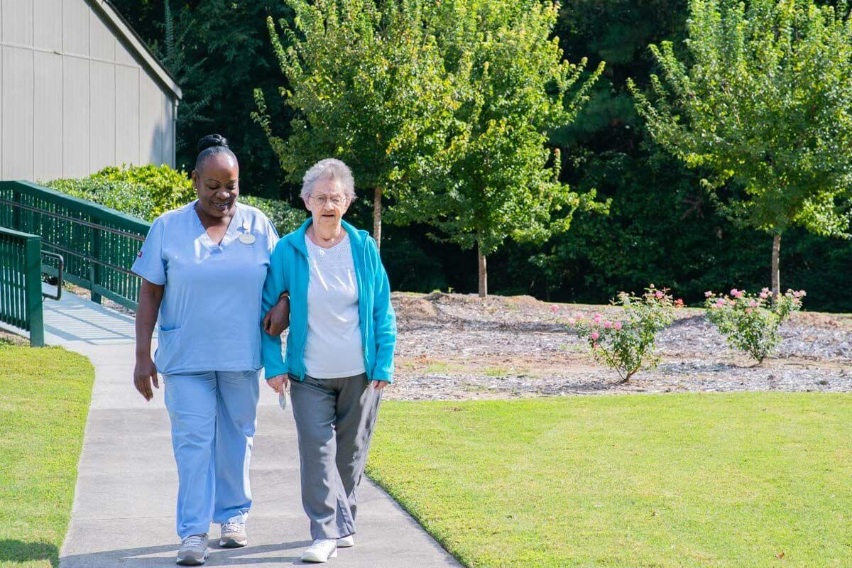 A caregiver and senior living resident walking and talking outside