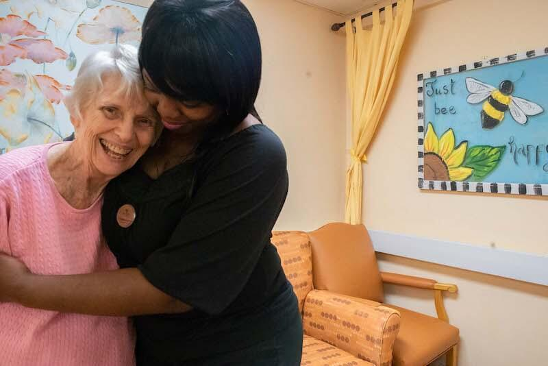 A caregiver hugging a senior living resident