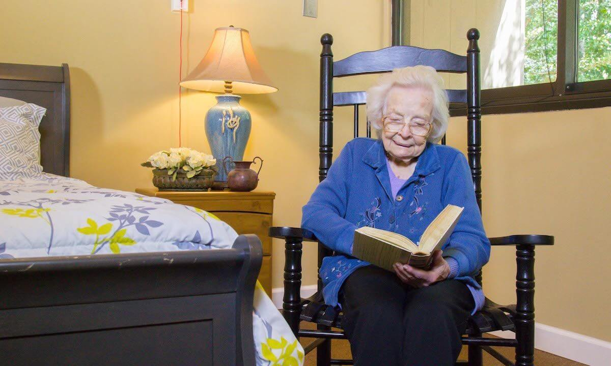 Senior resident sitting in a chair reading beside a bed