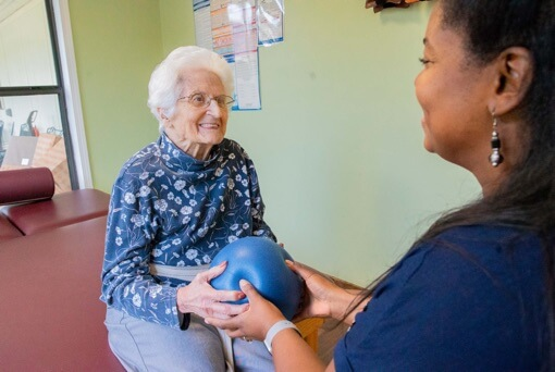 Therapy and Physician resident exercising with a medicine ball and handing to the caregiver
