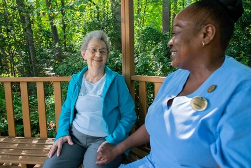 Short-Term Care resident sitting on a bench outside with a caregiver