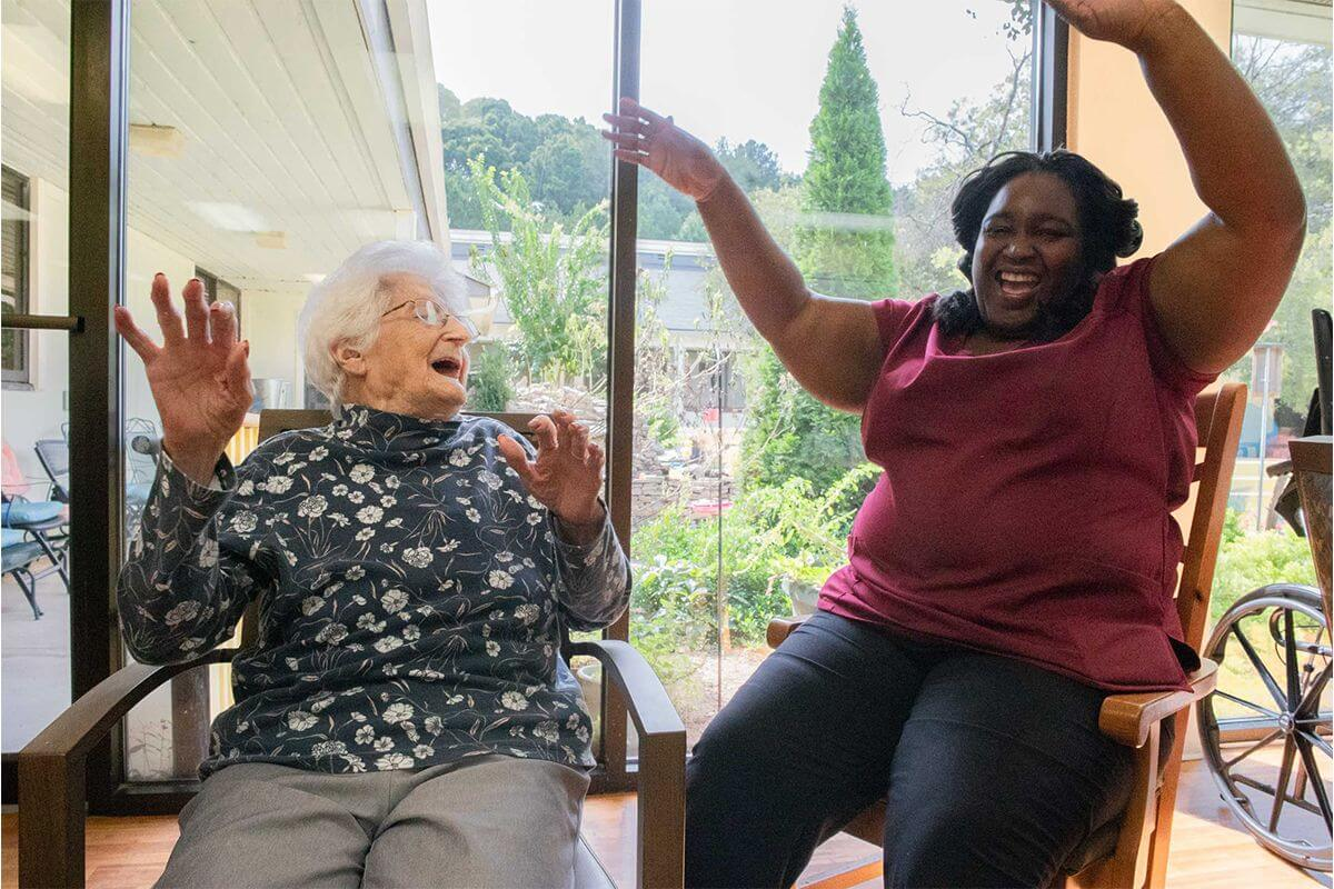 A senior resident and caregiver talking and laughing