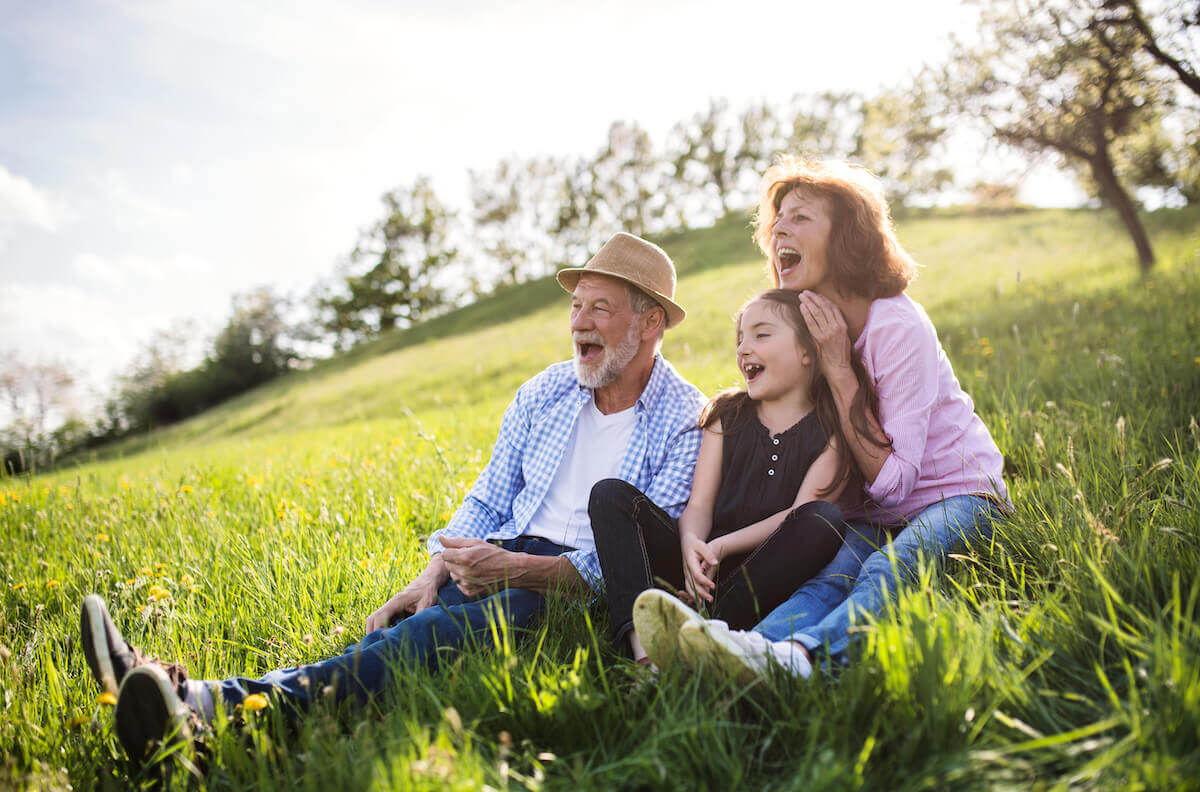 Grandparents sitting on a hill side with their grand daughter